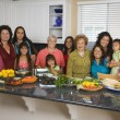 Foto Stock: Large Hispanic family in kitchen with food