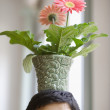 Close up of young adult man balancing potted flower on head — Stock Photo