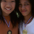 Portrait of two girls smiling with metals around neck — Стоковая фотография