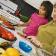 Hispanic grandmother and granddaughter preparing food in kitchen — Stock Photo