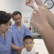 Doctor preparing injection for Asian boy in hospital bed — Stock Photo