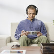 Man sitting on sofa wearing headphones — Stock Photo