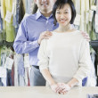 Asian male and female drycleaners smiling  — Stock Photo
