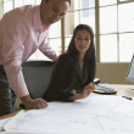 Businesspeople examining blueprints — Stock Photo