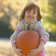 Young girl smiling and holding pumpkin outdoors - Stock Photo