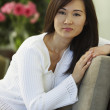 Asian woman sitting on chair — Stock Photo