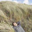 Asian man lying in dune grass — Stock Photo