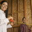 Hispanic couple using tape measure in construction site — Foto Stock