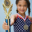 Hispanic girl holding medal and trophy — Stock Photo