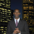 African businessman in front of urban buildings at night  — Stock Photo