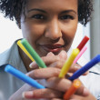 African American woman holding multicolored markers in hands — Stock Photo