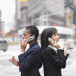 Two businesswomen standing while talking on cell phone — Stock Photo