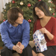 Couple opening gifts by Christmas tree — Stock Photo
