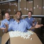 Three male warehouse workers joking around — Stock Photo #13221442
