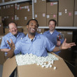 Three male warehouse workers joking around — Stock Photo