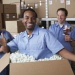 Three male warehouse workers joking around — Stock Photo #13221444