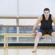 Man in athletic gear sitting in dance studio — Lizenzfreies Foto