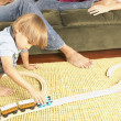 Young boy playing with trains on living room floor - Stock Photo