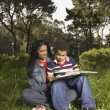 Mother and son reading in meadow - Stock Photo