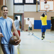 Man holding basketball with team warming up behind him — Foto Stock