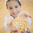 Pacific Islander girl standing in corn silo holding up handful of corn - Stock Photo