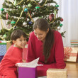 Brother and sister opening Christmas gift in front of tree - Stock Photo