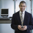 Stock Photo: Businessmwith cell phone next to computer stations