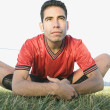 Male soccer player stretching in grass - ストック写真