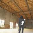 Stock Photo: Businesswoman standing in empty warehouse with blueprints