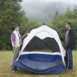 Indian couple putting up tent - Stock Photo