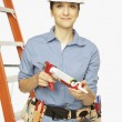 Hispanic female construction worker holding caulking gun — Stock Photo