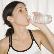 Hispanic woman drinking bottled water — Stock Photo