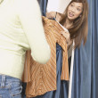 Asian woman peeking out from dressing room - Stockfoto