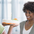 African American girl bringing mother birthday cake - Stock Photo