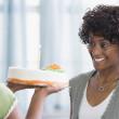 African American girl bringing mother birthday cake — Stock Photo