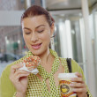 Businesswoman eating a donut — Stock Photo