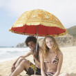 Young couple under sun umbrella on beach — Stock Photo