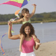 Hispanic mother and daughter flying kite on beach - Stock Photo