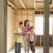 Family with blueprints on construction site - Stock Photo