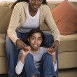 Portrait of mother and daughter sitting in living room - Stock Photo