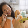 Young woman talking on her cell phone while holding a bag of groceries — Stock Photo