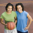 Portrait of two teenage girls with basketball on court - ストック写真