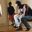 African man lifting dumbbell while son watches - ストック写真