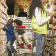 African American mother with young sons in health food store — Stock Photo