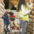 Stock Photo: African American mother with young sons in health food store