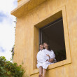 Couple in bathrobes sitting in window — Stock Photo