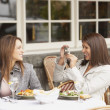 Woman having her photograph taken by other woman at lunch - Stock Photo