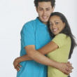 Young couple hugging and smiling for the camera — Stock Photo
