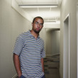 Portrait of a young man standing in a corridor — Stock Photo