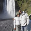 Couple in winter clothes hugging in front of waterfall — Foto de Stock